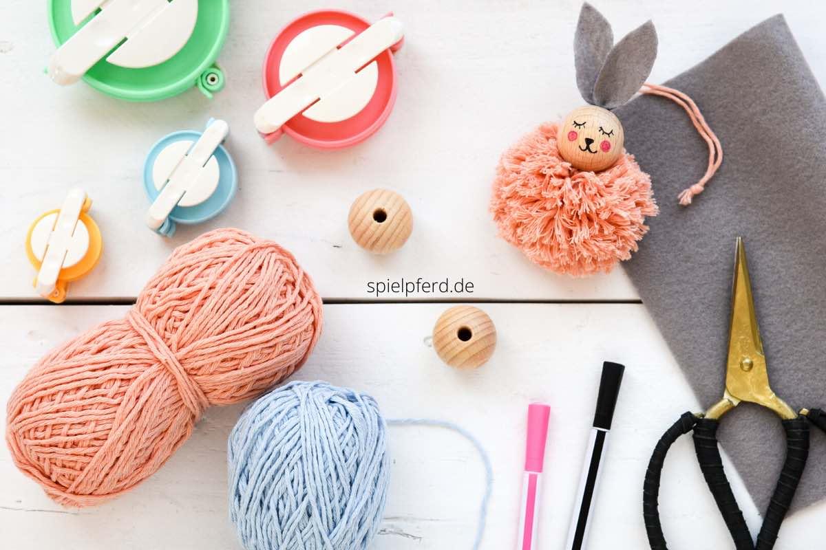 Osterdeko basteln mit Kindern. DIY-Idee zu Ostern. Dekoration zu Ostern. Niedlicher Anhänger: Hase aus Holzkugel und Pompon (Bommel). Osteranhänger basteln.